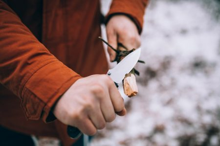 A man uses a knife to whittle a stick out hiking - The Skilled Survivor