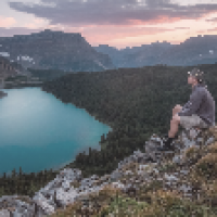 Hiking man sitting on rocky mountain overlooking pretty blue lake - The Skilled Survivor